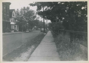 View looking south in the direction of W. 231st St. on Albany Crescent, Jul 9, 1950.  The building on the left is now a church and the house still stands as well.